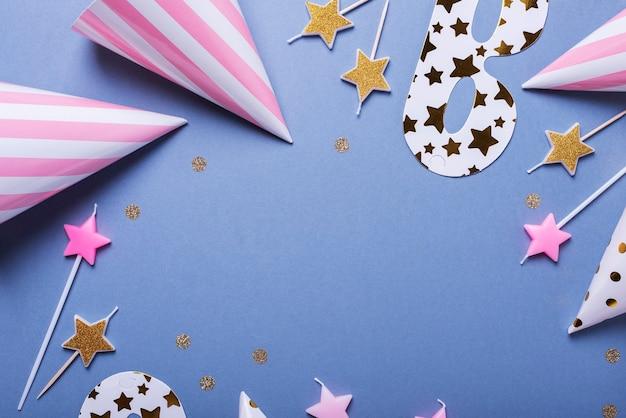 Carta di invito festa di compleanno con cappelli da festa, maschere e candele, vista dall'alto verso il basso con copia spazio per il testo