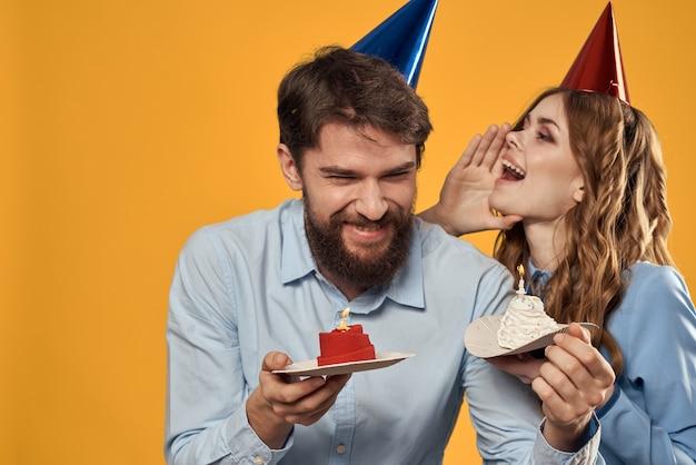 Festa di compleanno uomo e donna su un giallo in cappelli con una torta in mano