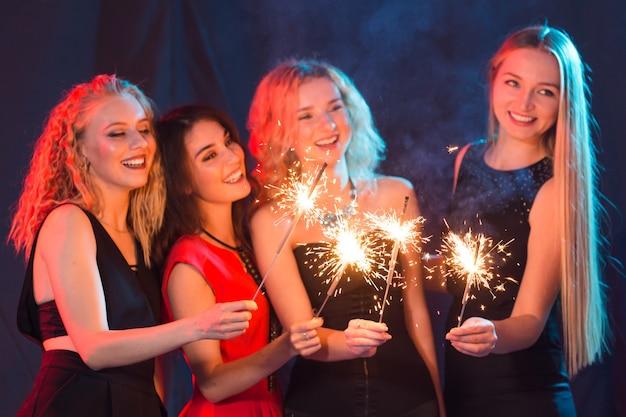 Festa di compleanno, capodanno e concetto di vacanze - gruppo di amiche che celebrano le stelle filanti in mano.