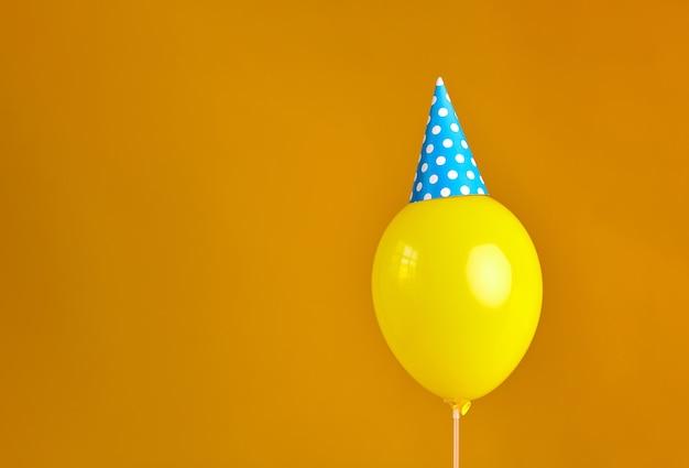 Palloncino giallo festa di compleanno con cappello da festa blu isolato su sfondo arancione
