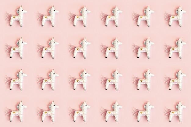 Modello di unicorno di pinata di compleanno sopra la parete pastello rosa