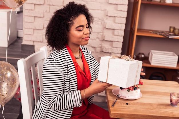 Sorpresa di compleanno. bella donna afro-americana che guarda il suo presente mentre è seduto al tavolo