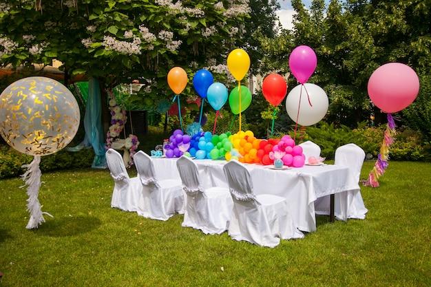 Tabella di compleanno con palloncini arcobaleno. vacanze estive nel parco.