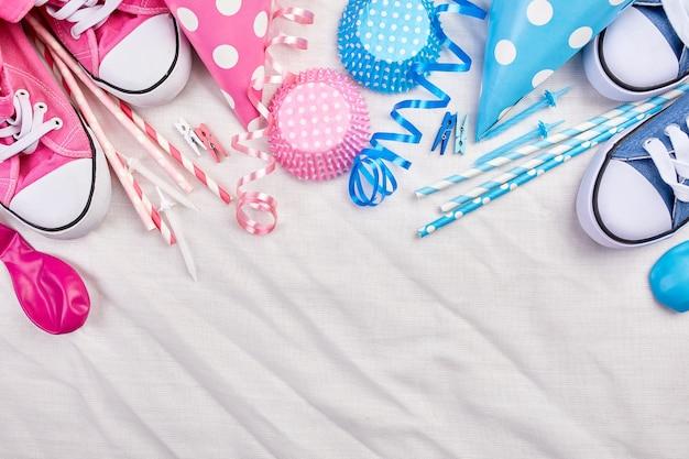 Compleanno gemelli ragazzo e ragazza distesi, vista dall'alto e copia spazio per testo, cornice o sfondo con elementi del festival rosa e blu, cappelli da festa e stelle filanti, biglietto di auguri per la festa.