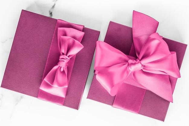 Matrimonio compleanno e concetto di branding femminile confezione regalo rosa con fiocco di seta su sfondo marmo ragazza b...