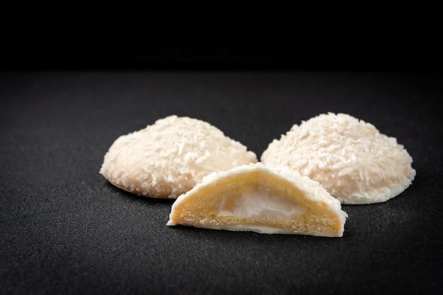 Biscotti biscotto con ripieno di cocco sul nero.