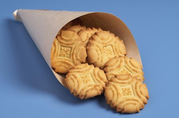 Biscotti di pasta frolla biscotto in sacchetto di carta sul tavolo blu