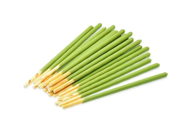 Biscotto in stick con tè verde aromatizzato su fondo bianco.