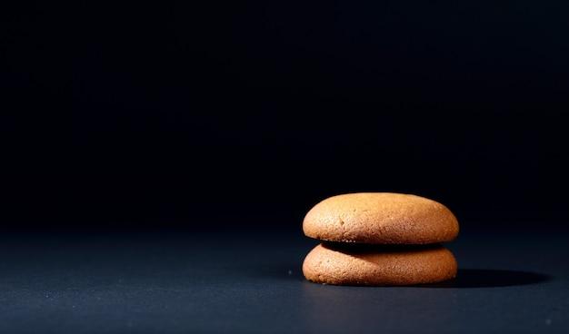 Biscotti ripieni di crema al cioccolato. biscotti alla crema di cioccolato. biscotti al cioccolato marrone con ripieno di crema su sfondo nero.