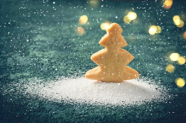 Biscotti a forma di albero di natale in un cumulo di neve di zucchero a velo Foto Premium