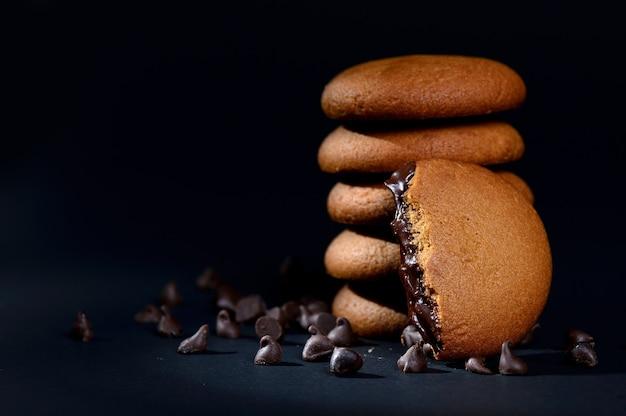 Biscotti - pila di deliziosi biscotti alla crema ripieni di crema al cioccolato su sfondo nero