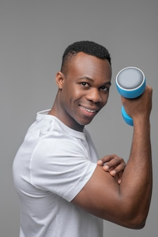 Biseppi, sport. felice sorridente giovane uomo dalla pelle scura in maglietta bianca con manubri blu che mostra bicipiti pompati