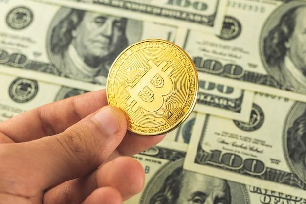 Bitcoin contro dollari americani, concetto di scambio di criptovaluta, foto di sfondo aziendale con mano e moneta d'oro