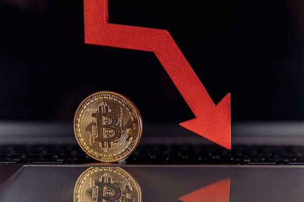 Bitcoin e freccia giù sulla criptovaluta del laptop la caduta del valore di bitcoin
