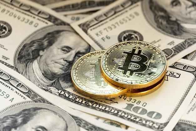 Bitcoin sullo sfondo di 100 fatture del dollaro.