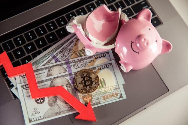 Bitcoin salvadanaio rotto e freccia verso il basso su criptovaluta in contanti in dollari e tema di investimento la caduta di btc