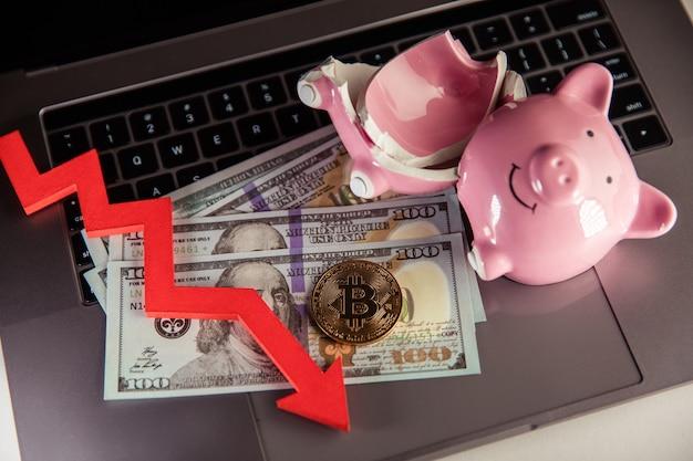 Bitcoin rotto piggy bnak e freccia giù closeup criptovaluta e concetto di investimento