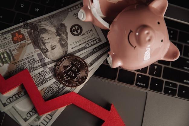 Bitcoin rotto piggy bnak e freccia giù closeup criptovaluta e tema di investimento