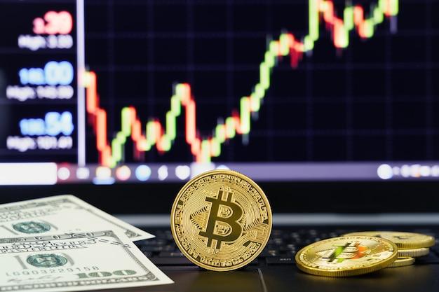 Bitcoin moneta e banconote sul computer della tastiera. primo piano di monete in criptovaluta bitcoin con grafico dei prezzi di mercato di scambio sullo sfondo