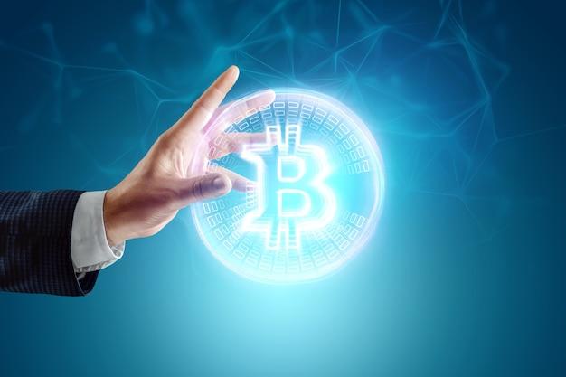 Moneta bitcoin nella mano di un uomo d'affari, ologramma. valuta digitale, denaro virtuale e criptovaluta, tecnologia blockchain.