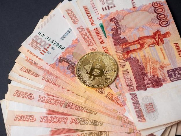 La moneta bitcoin si trova sullo sfondo dei rubli russi. mining di criptovaluta e concetto di mining. vista dall'alto, piatto.