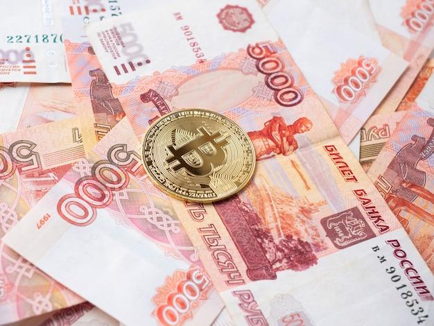 La moneta bitcoin si trova sullo sfondo dei rubli russi. mining di criptovaluta e concetto di mining
