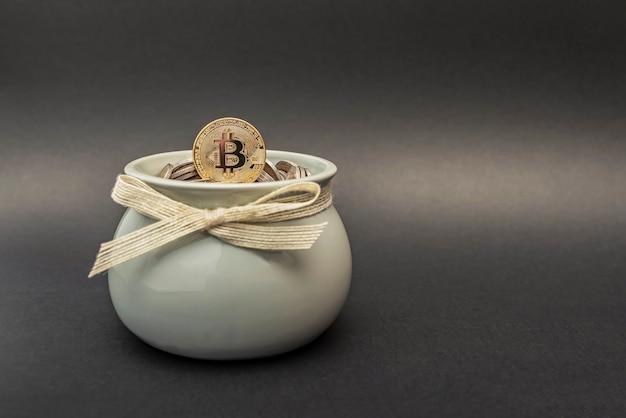 La moneta bitcoin si trova nel salvadanaio sulle monete fiat. accumulo di criptovaluta e simbolo di investimento. copia spazio