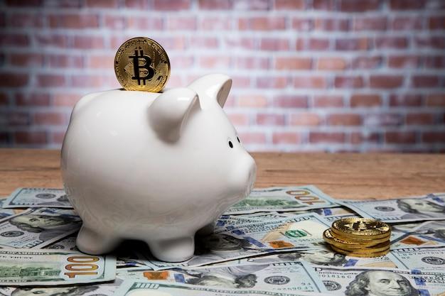 Moneta bitcoin sulla parte superiore di un salvadanaio, risparmiando denaro acquistando bitcoin come oro digitale.