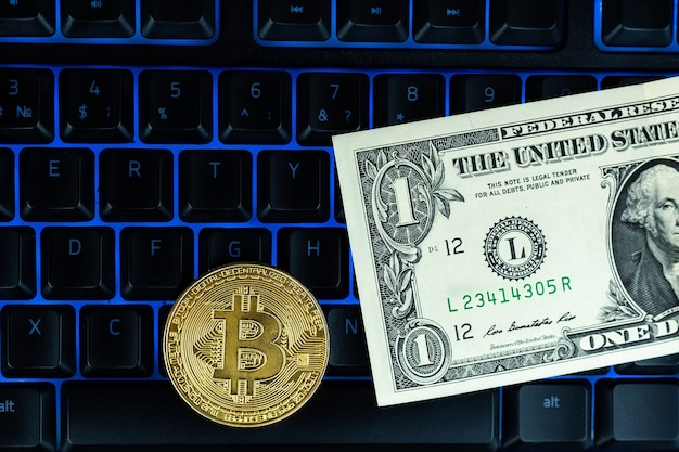 Moneta bitcoin con laptop e dollari usa. bitcoin monete d'oro su un portatile di banconote del dollaro ufficio sfondo nero mobile.