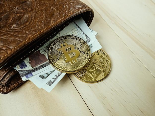 Il bitcoin nel portafoglio in pelle di coccodrillo sulla tavola di legno.