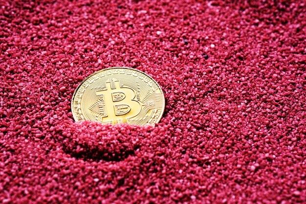 Criptovaluta bitcoin circondata da sabbia rossa e spazio di copia