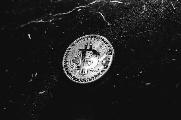 Bitcoin su uno sfondo scuro. la criptovaluta è la valuta del futuro. la moneta moderna sta conquistando l'economia.