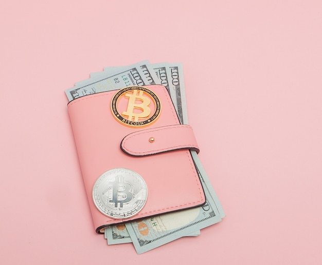 Bitcoin e dollari in un portafoglio rosa sul rosa