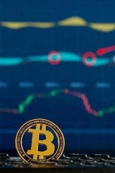 Moneta d'oro bitcoin e sfondo grafico sfocato