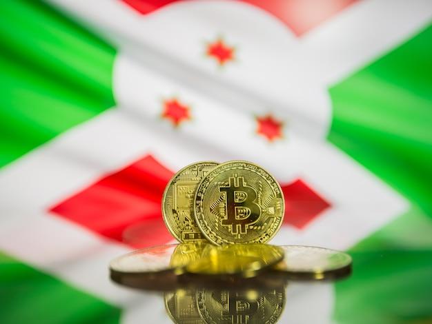 Bitcoin moneta d'oro e bandiera sfocata dello sfondo del burundi. concetto di criptovaluta virtuale.