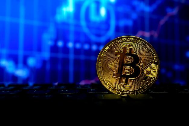 Moneta d'oro bitcoin su tastiera e grafico