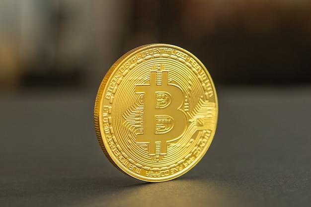 Moneta d'oro bitcoin e sfondo sfocato. concetto di criptovaluta virtuale.