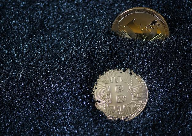 Bitcoin e litecoin su granuli scintillanti blu, sabbia. moneta elettronica