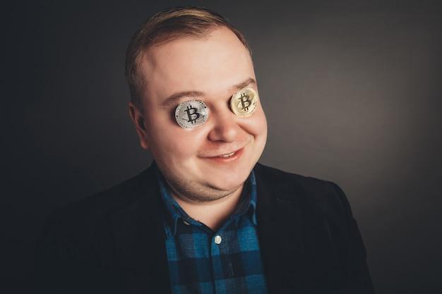 Amante maschio bitcoin con moneta d'oro sui suoi occhi