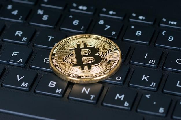Bitcoin moneta metallica sulla tastiera di lettere del computer nero