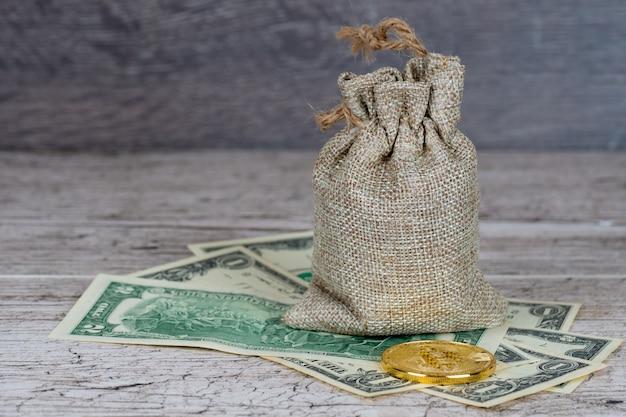 Bitcoin moneta metallica su banconote in dollari vicino al sacco di iuta pieno
