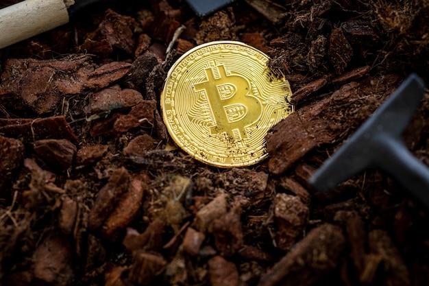 Bitcoin mining bitcoin cosparso di terra accanto ad esso è una piccola pala