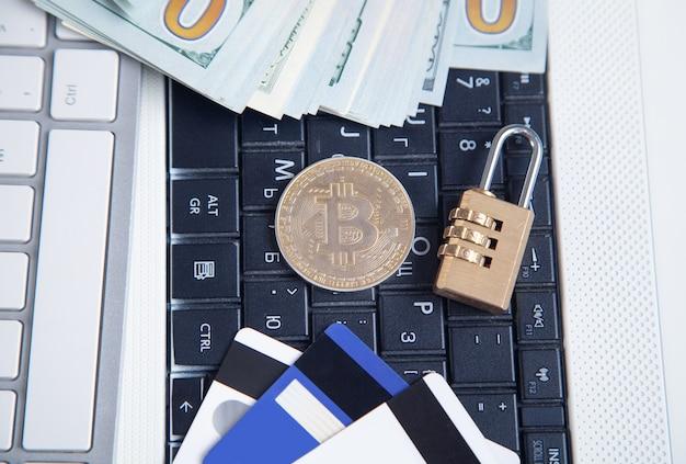 Bitcoin, denaro, carte di credito e lucchetto sulla tastiera del computer bianco.