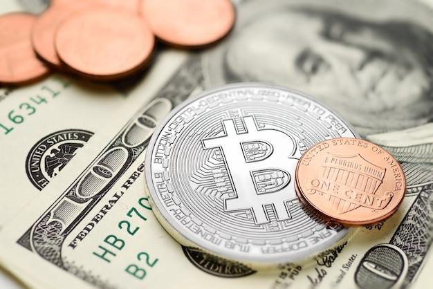 Bitcoin e monete da un centesimo sulle banconote in dollari usa. concetto di scambio di denaro elettronico