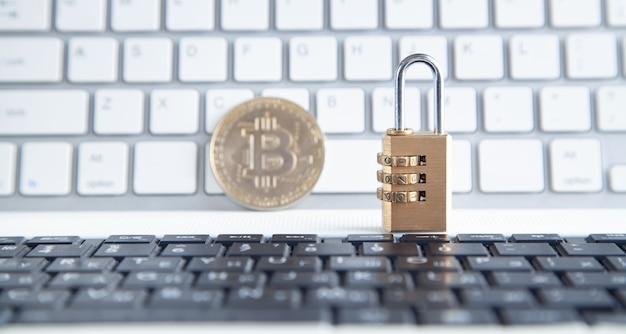 Bitcoin e lucchetto sulla tastiera del computer bianco.