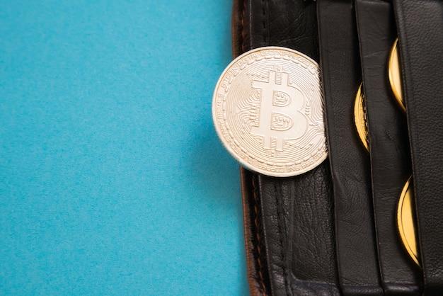 Bitcoin che sporge da un portafoglio o superficie blu.