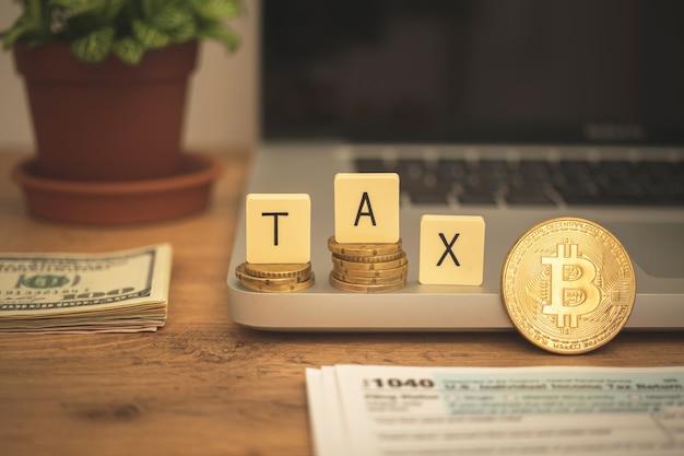 Bitcoin e sfondo fiscale. criptovaluta e concetto di tassazione. desktop aziendale con laptop e denaro