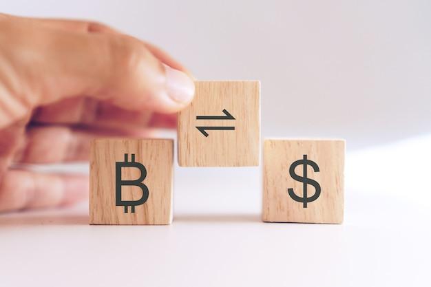 Scambio o scambio di bitcoin in segno di dollaro nel mercato azionario sul cubo di legno con mano tenerlo.