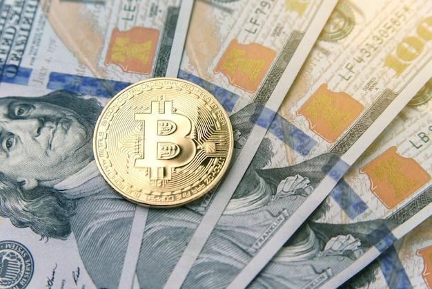 Bitcoin su banconote in usd da cento dollari. investimento di denaro virtuale. affari di criptovaluta