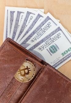 Bitcoin con dollari di carta nella vista dall'alto del portafoglio. trading di criptovaluta virtuale e concetto di investimento